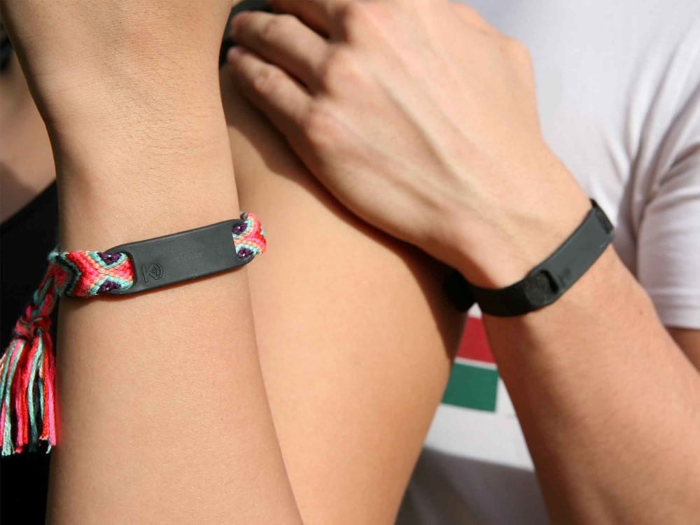 A lady and man's arms wearing a K-pay Mavericks contactless payment straptag with ribbon to tie to wrists.