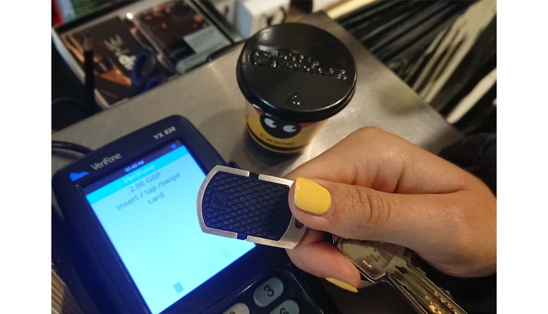 Woman paying for some chocolate with a K-pay New York contactless payment keyfob,