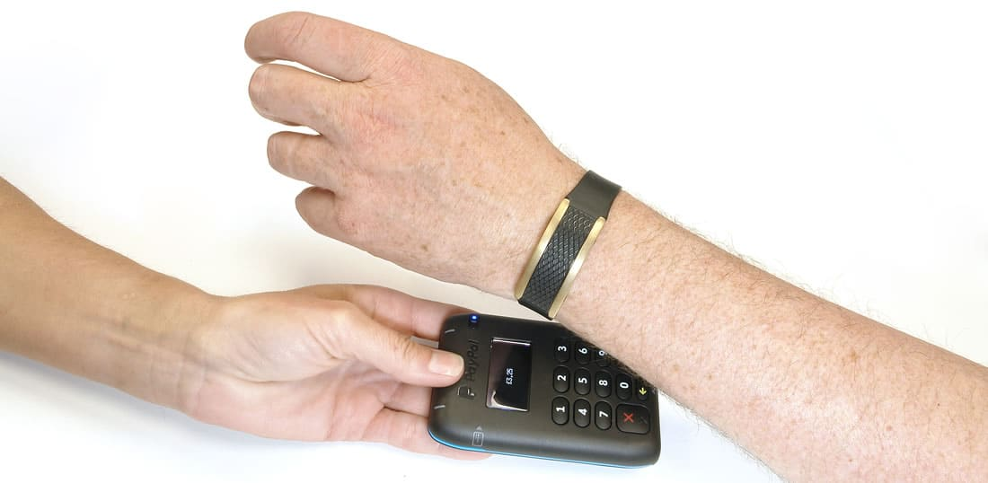 A man paying with a K-pay Monaco stylish contactless payment bracelet whilst a woman holds the payment terminal for him